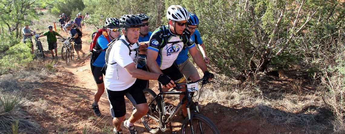 Veteran being assisted up a steep mountain bike climb.