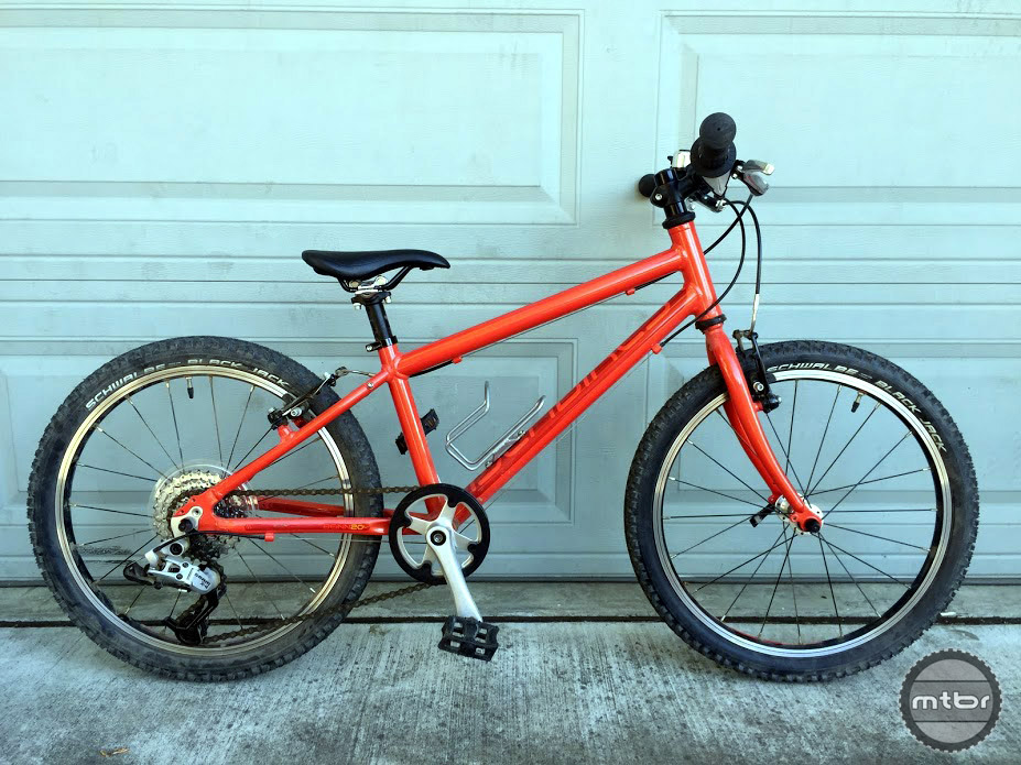 "A side view of the Islabikes Beinn 20 L with an 11"" aluminum frame and rigid, cromoly fork shown here in orangey-red color."