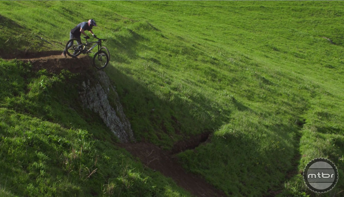 Brandon switches bikes and hops on to the bike while dropping into a cliff.