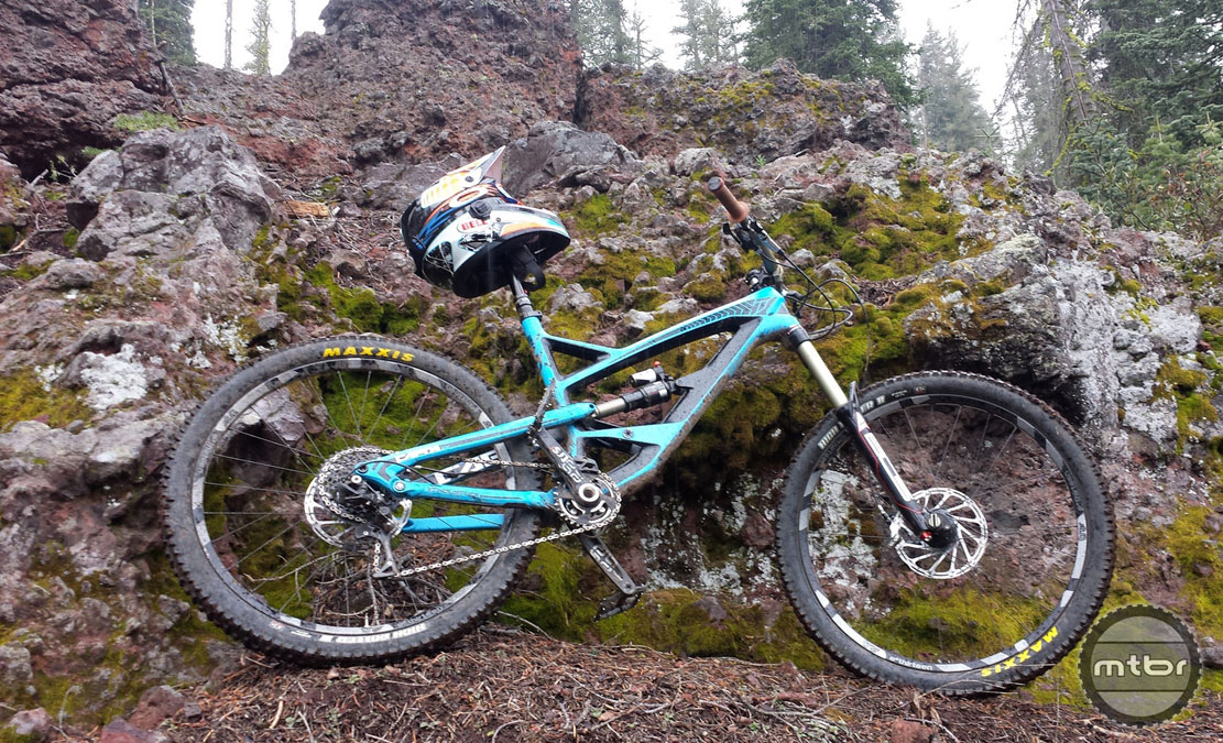 The YT Capra bike leaning against a cliff.