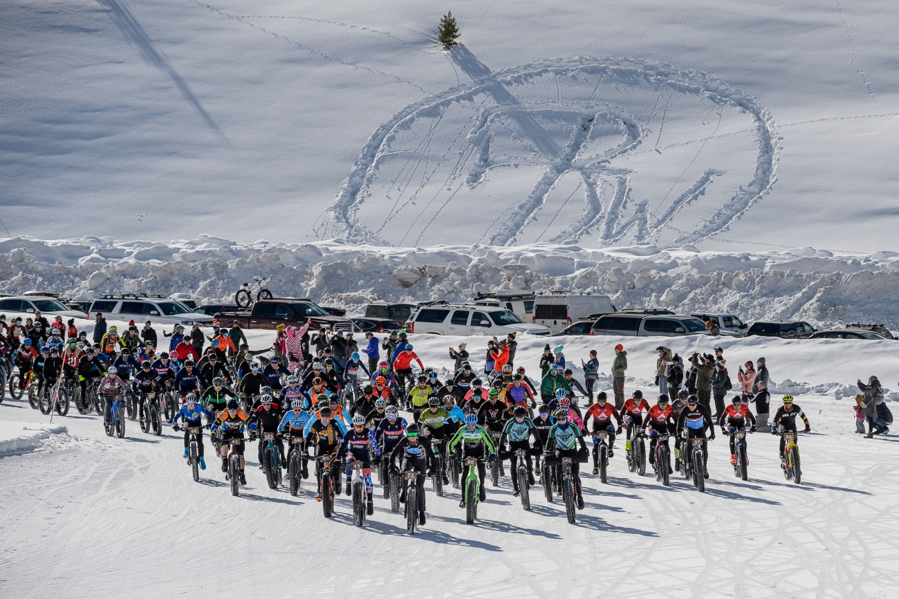 With a snowy version of the Fat Bike World Championship logo looming in the background, 143 big tire devotees take off from the start line in Crested Butte, Colorado. Photo by Robby Lloyd/Lucid Images