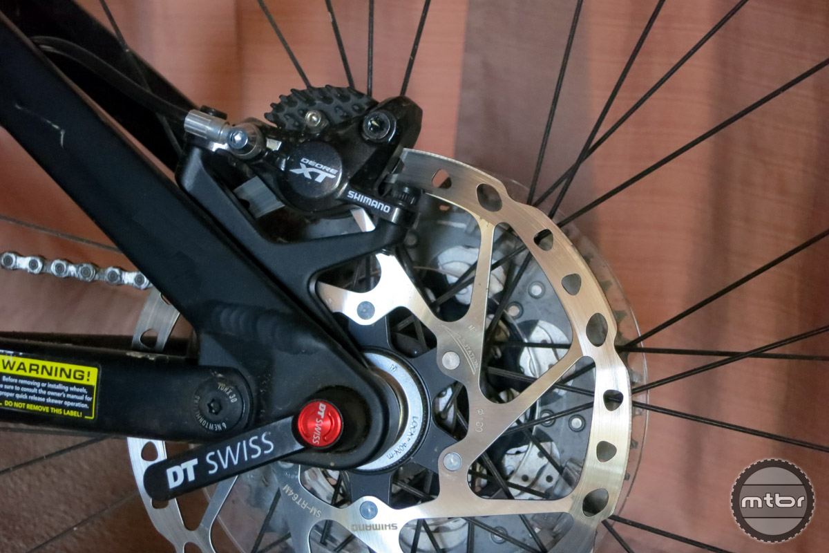 The rear brake caliper mounts directly to the X12 thru-axle in order to maintain better alignment and to distribute braking forces into the axle instead of the frame.