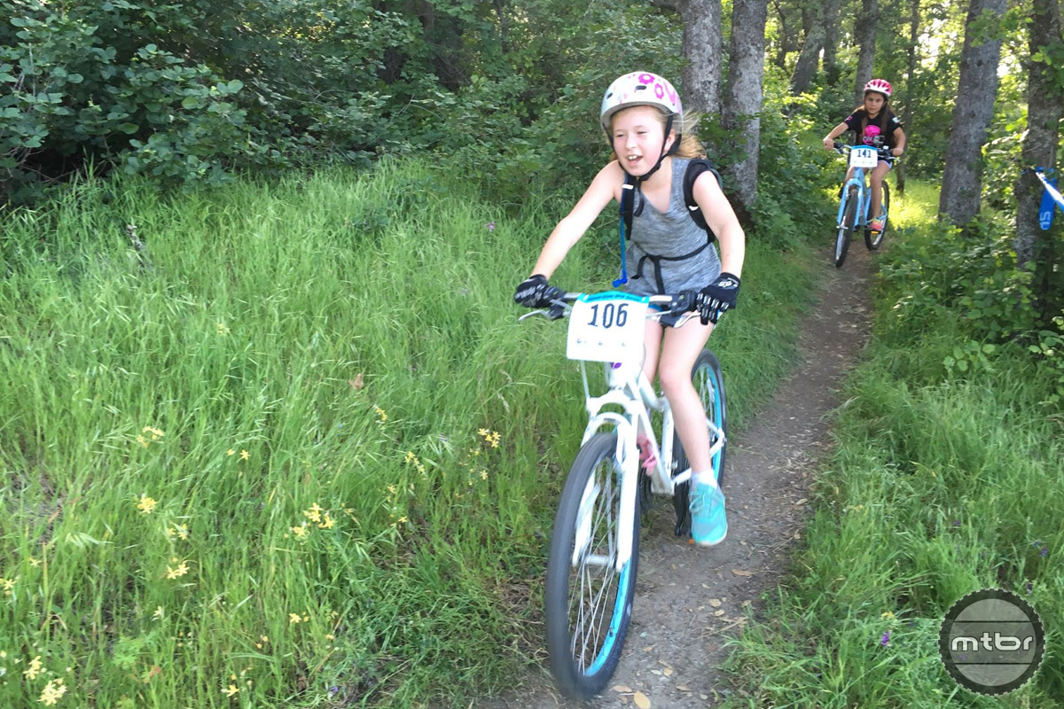 Grom girls racing the singletrack in the trees.
