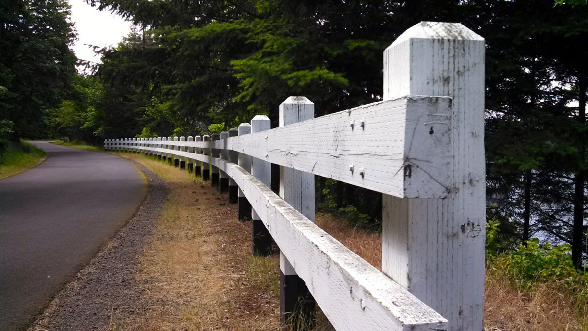 The characteristic white wooden guardrails of the Historic Columbia River Highway.
