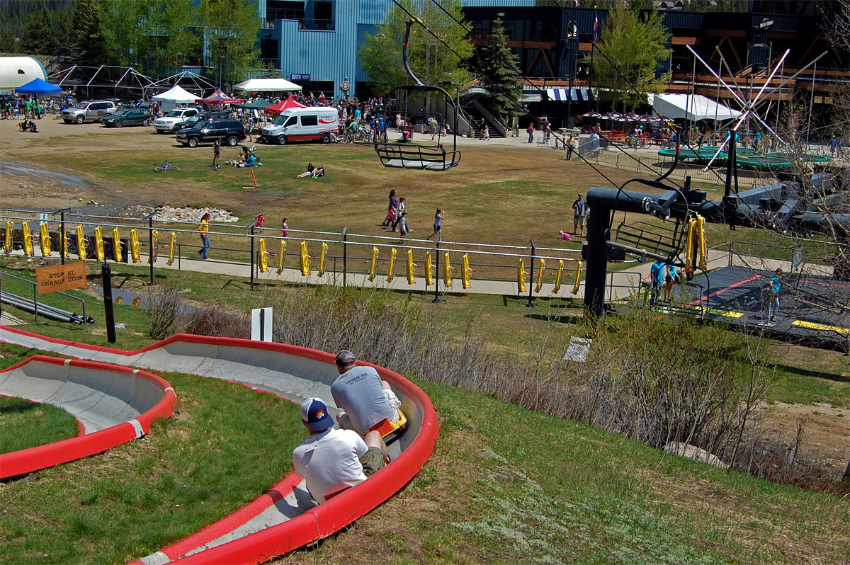 Guests ride Colorado's longest (3,030 feet) Alpine Slide with views of the base area - by Tana Hoffman, Winter Park Resort