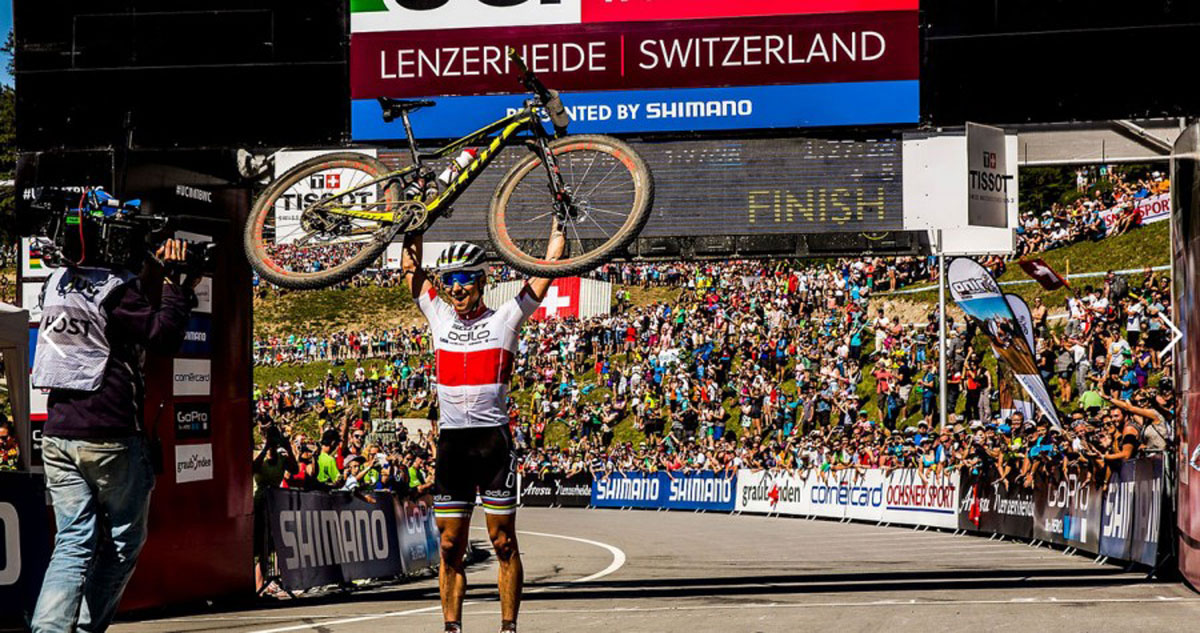 Schurter shows off his new bike at the finish line of the World Cup in Lenzerheide, Switzerland. Will he strike a similar pose in Rio?