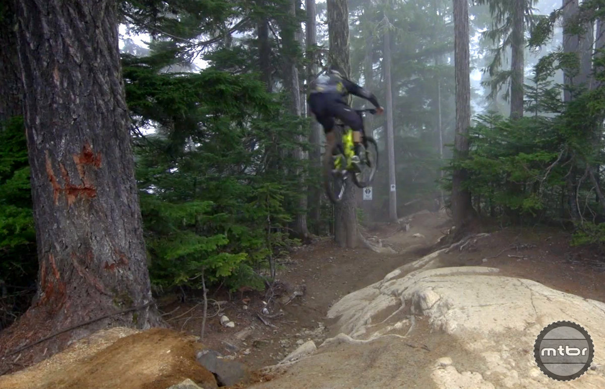Rémy jumps in singletrack and lands in roots and rocks at full speed.