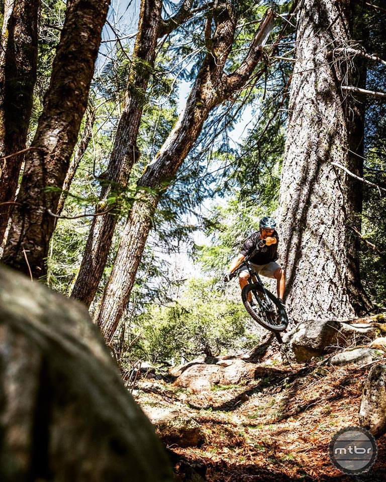 Ryan Thym sends it off a root booter on Rattlesnake Creek trail. Photo by James Adamson – Dropmedia.tv