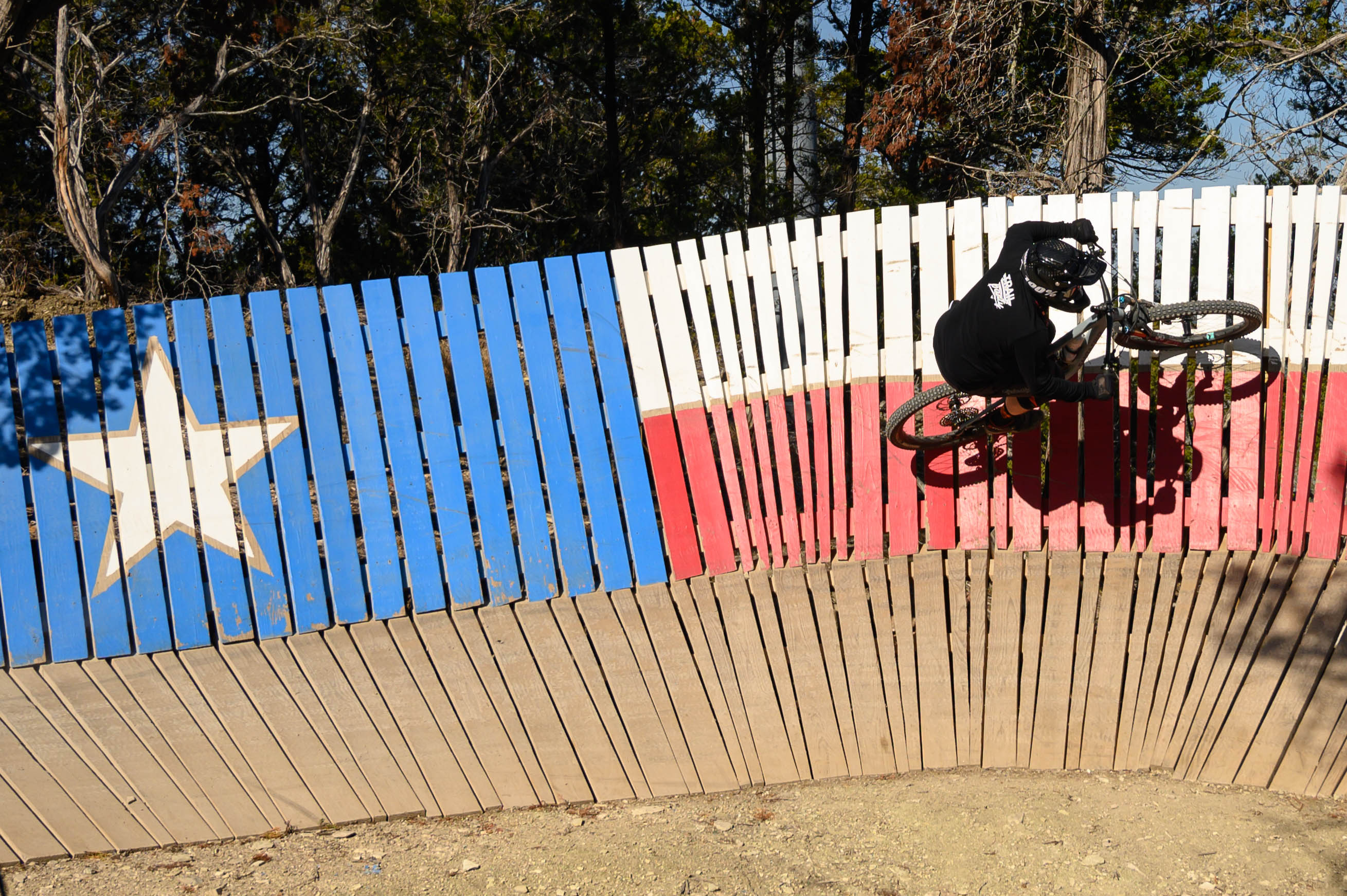 Local racer and Team Trail Party's graphic designer, Steven Mullins, hits the Texas flag wall ride on Viper's Den.